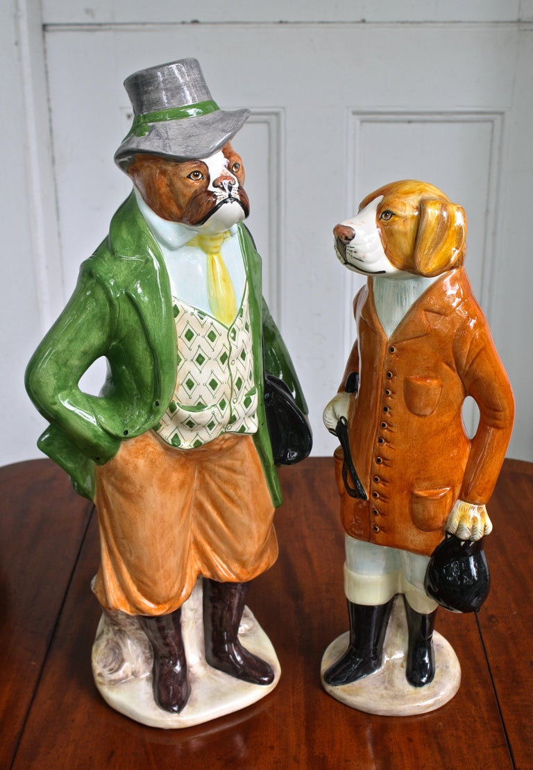 Two Italian ceramic dogs; dressed as an equestrian couple from the late 19th century. The shorter, appearing to be a foxhound 'whipper-in': 20 1/4 inches tall by 8 inch diameter; bearing the mark