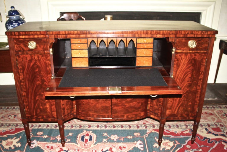 A Bankson and Lawson 'School', Sheraton manner sideboard with a English influenced fall-front butler's secretary drawer. Exceptionally vibrant crotch and flame mahogany veneers and bandings; the secretary desk is fitted with sharply contrasting