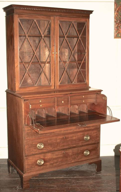 A Federal period pale mahogany Hepplewhite manner secretary bookcase with very fine rope and string inlays. Finish, glass, brasses and locks all original. In two parts: Three shelf bookcase with diamond mullioned doors, atop a lower case containing