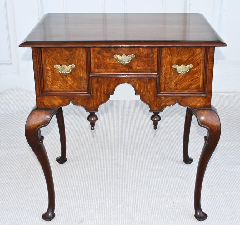 A mid-eighteenth century hand-planed and hand-carved walnut lowboy, originally intended as a dressing table.  Walnut burl veneers on its drawers and case front.  Inverted finials at the skirt of its center kneehole arch.  Particularly graceful