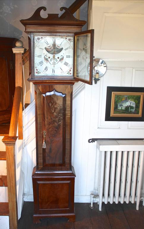 A seven foot tall Regency period clock with a finely detailed mahogany case and paint decorated face. The mahogany case includes solids as well as crotch and flame veneers, with wide grained bandings.  The complex elements of its face paint