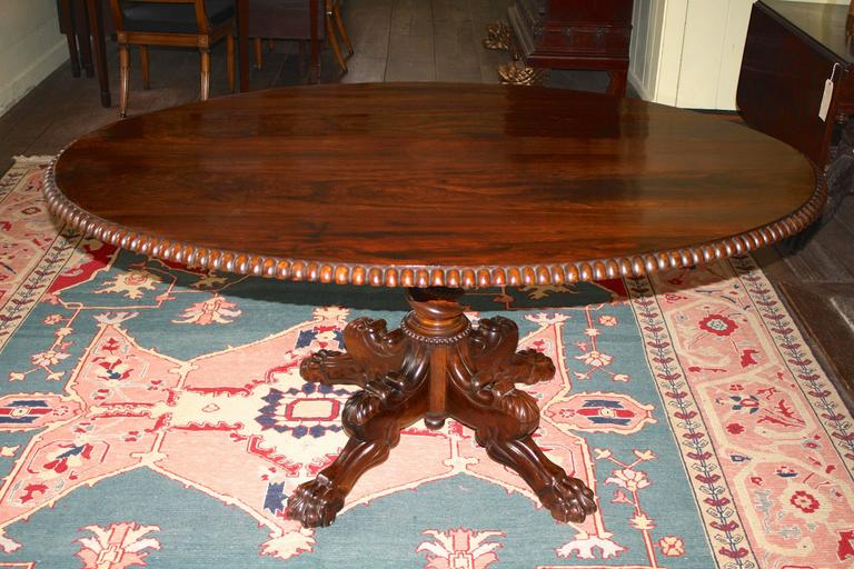 Grand and profusely hand-carved solid rosewood oval tilt-top center table, made in India during the reign of William IV; acquired by British watercolorist C. Bigot whose stamp is impressed on the table's block. (Image #9) Bigot created a series of