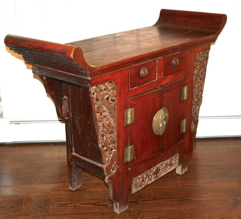 An ornate South China altar cabinet of the Tongzhi period. Pierce-carved jabots and a frieze panel decorate the trestle structure; usually open, yet in this case enclosed by side and back panels, and fronted by two drawers over two doors. The
