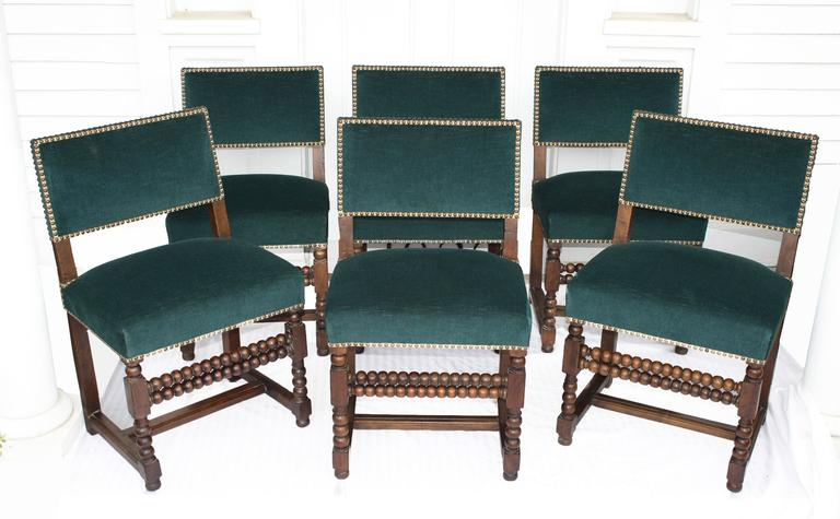 An extraordinary set of six mid-17th century Louis XIII late Renaissance period dining side chairs. Hand-turned and carved oak, dual turned front stretchers, flat H-stretchers, and solid planed oak back-boards; recently re-upholstered to today's