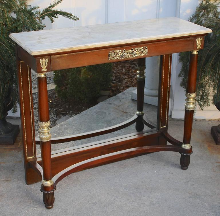 A French Restauration period marble-top mahogany pier table with exceptionally fine ormolu mounts of harpies and lyres to its apron. Three turned ormolu elements on the frontal columns; including three-tiered complex foliate turnings midway on each.