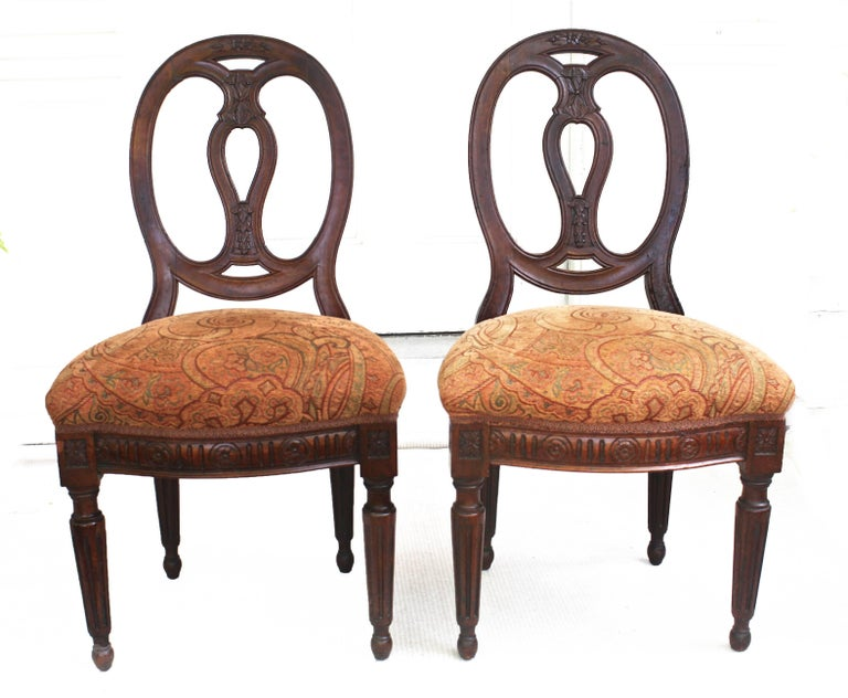 Elaborately hand-carved walnut chairs with thickly-boxed velvet upholstered seats. Oval carved back splats. Turned and fluted legs. Decoratively carved seat side and front frames. Likely Nord-Ovest origin. Served for decades as backgammon chairs.