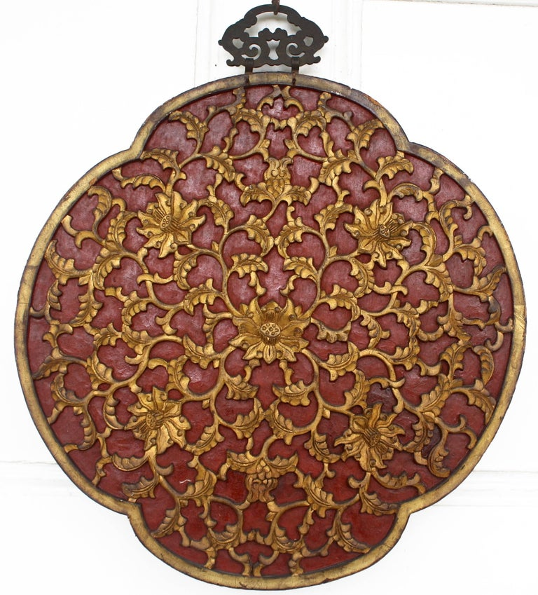 Dating from the reign of the Jiaqing Emperor (1796-1820), a two sided quatrefoil panel featuring a pheasant in foliage on ebony background on its primary side; with parcel-gilt foliate vine carvings on red background, en verso. Original hand-forged