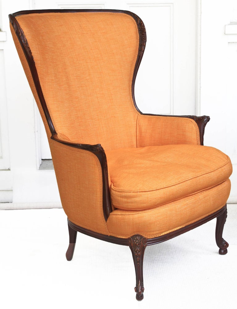 A very comfortable cushioned French form of 'wing chair' that first debuted mid-18th century. This Napoleon III period 19th century version has a carved 'acajou' frame that harkens back to its Louis XV period origin. Eccentric sleek seating,