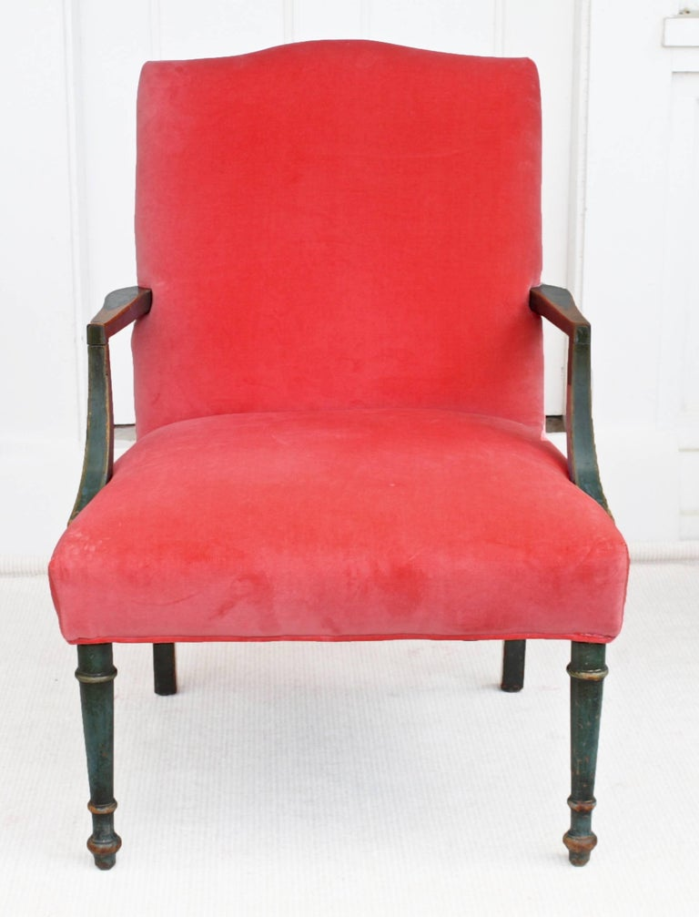 A rare and unusual English Regency period open armchair appearing to be in its original mottled blue-green paint, with traces of worn gilding on its front leg turnings. Hand-wear to painted surfaces reveals the color and graining of a yew wood