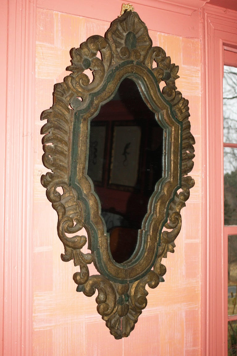 An ornately pierce-carved foliate framed elongated hexagonal mirror. The emerald green paint and water gilding appear to be original, with minimal 'in-painting' conservation. Ex: the Continental furniture collection of a National Historic Register