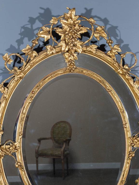 Receive our new selections direct from 1stdibs by email each week. Please click Follow Dealer below and see them first!  The beautiful oval of this antique gold leaf French mirror circa 1875 is wreathed with a trailing vine of grape leaves and