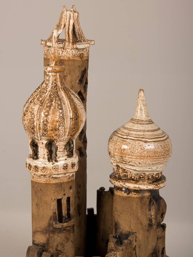 A vintage Polish fantasy castle circa 1950 made by hand of earthenware with three spires set within a wall. The fairy tale appearance of this castle relates to those seen in France that inspired the Disney castle for Sleeping Beauty.