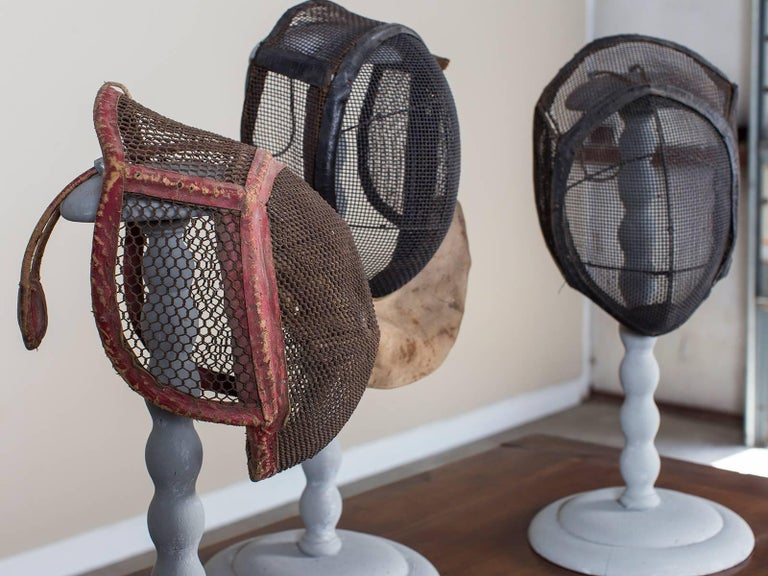 The unique shape of these antique French fencing masks, circa 1910 with their wire mesh protective guards set upon heavy iron frames are here displayed effectively upon painted wooden wig stands from 19th century, France. Each French fencing mask