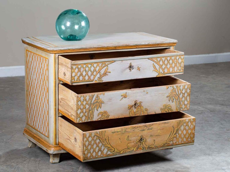A charming antique German Biedermeier painted chest of drawers, circa 1830. The handsome Rococo design of the refreshed painted finish features a hand-painted design of trellis pattern on each side while on the front the trellis frames the central