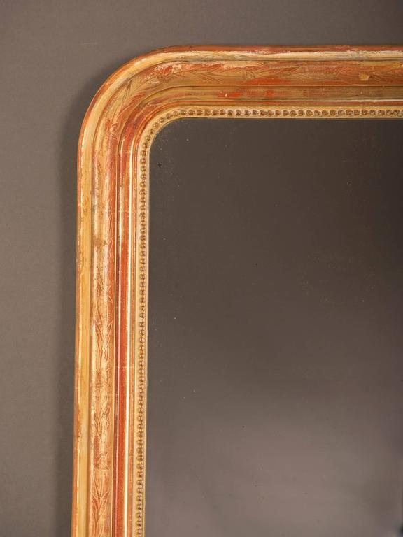 A gorgeous Louis Philippe style antique French gold leaf frame surrounding the original mirror glass circa 1880. Please note both the beautiful proportion of width to height as well as the exceptional beauty of the original gold leaf that has worn