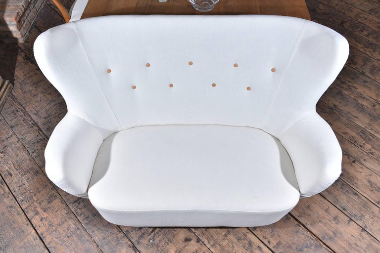 Small Danish settee, most likely made by Carl Malmsten. It has his typical birch legs. It is upholstered in a white linen with Swedish leather buttons.