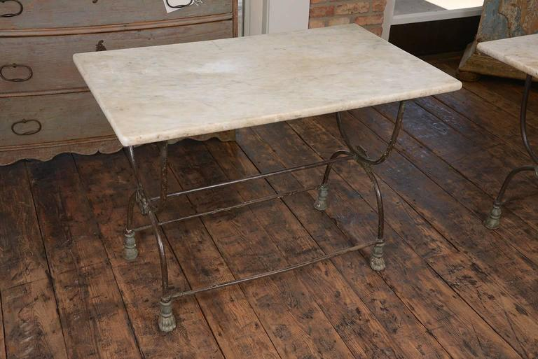 Nice pair of iron and marble butcher tables from France, elegant lines and honed marble tops. Some paint remains on the iron.
