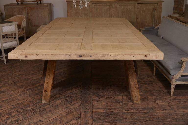 Amazing large scaled French dining table on two saw horses, wood is a French oak that has been stripped- originally the top was a door, one piece of remarkable wood. An incredible table. The top is 3 inches thick.