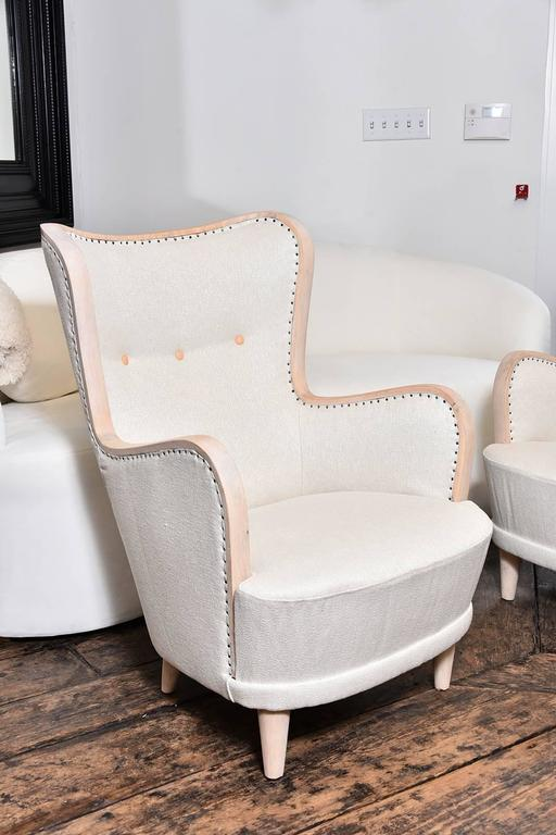 Early 20th century pair of Swedish wing chairs with exposed wood frame, covered in vintage linen. Very beautiful, circa 1930.