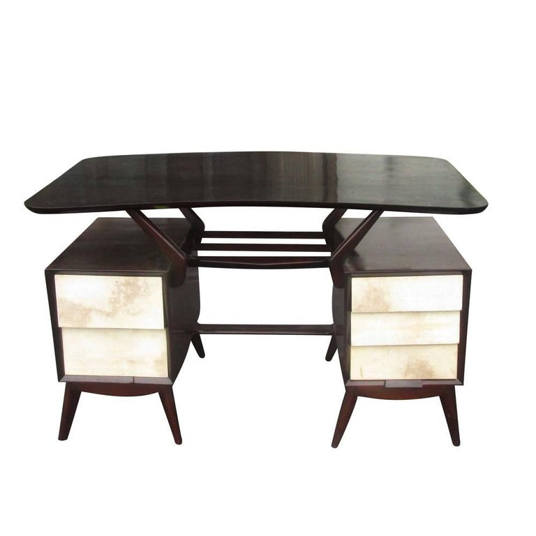 A vintage ebonized Italian desk with goatskin parchment drawers. This desk has a kidney-shaped top floating over two desk pedestals with splayed legs.