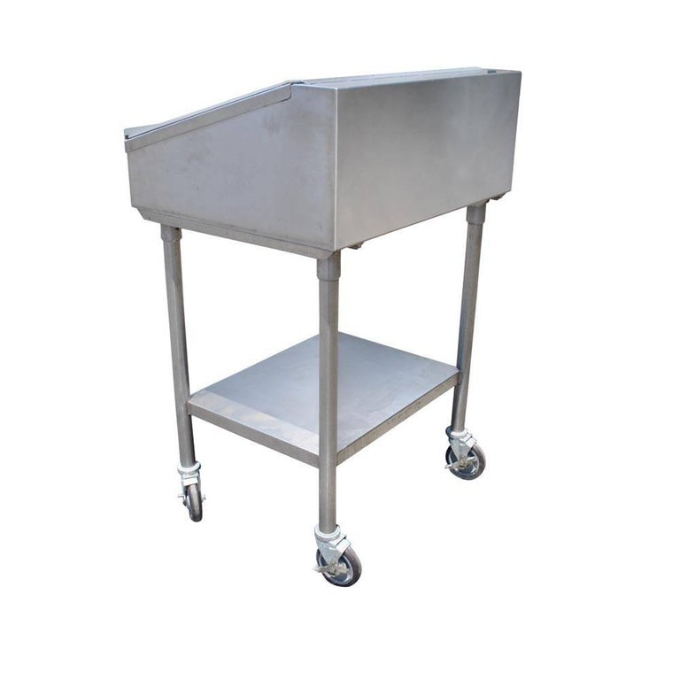 Industrial factory stainless steel standing desk.   Great example of a vintage stainless industrial desk.  Top opens for storage. On casters.  Would work well in restaurants and other reception areas.