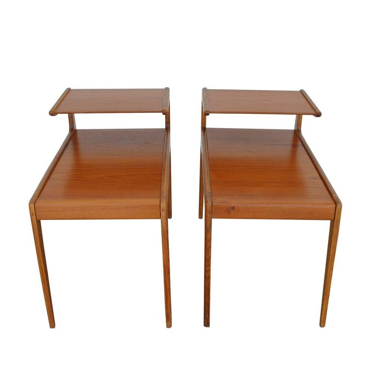 A pair of vintage Scandinavian end tables by Kurt Ostervig. Features two-tiered design and a continuation of the back legs of the tables, giving the tables a seamless quality to their design. With the prominent angles and surfaces of Scandinavian