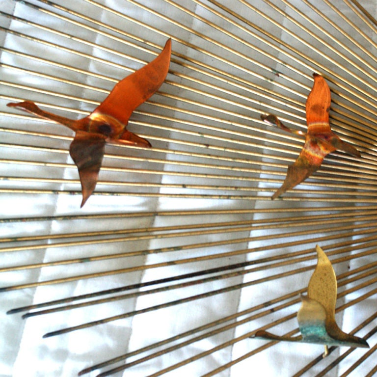 A Mid-Century Modern brass wall sculpture from Curtis Jere featuring multi-color birds in flight.