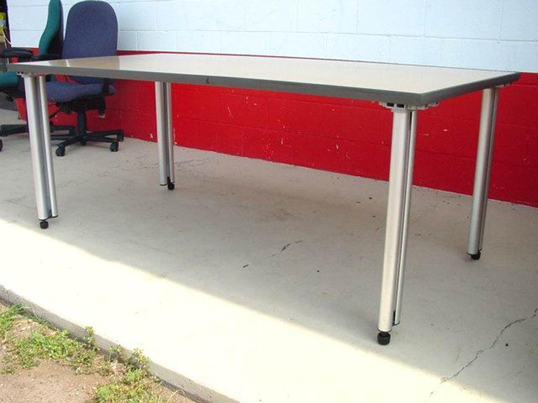 This is a Knoll Propeller modular table. This version has the wooden top, instead of laminate. The tabletop edges are coated with a rubber layer. A diagram underneath the table shows the various ways these tables can be arranged. The table legs