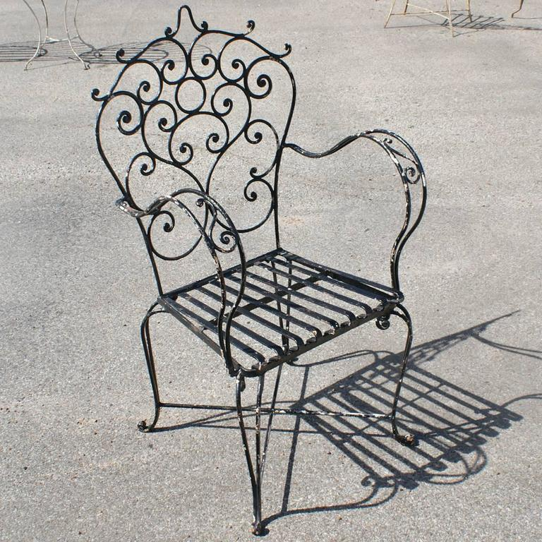 Vintage wrought iron table and chairs   (two) arm chairs and (two) side chairs No glass top Measures: Table 35