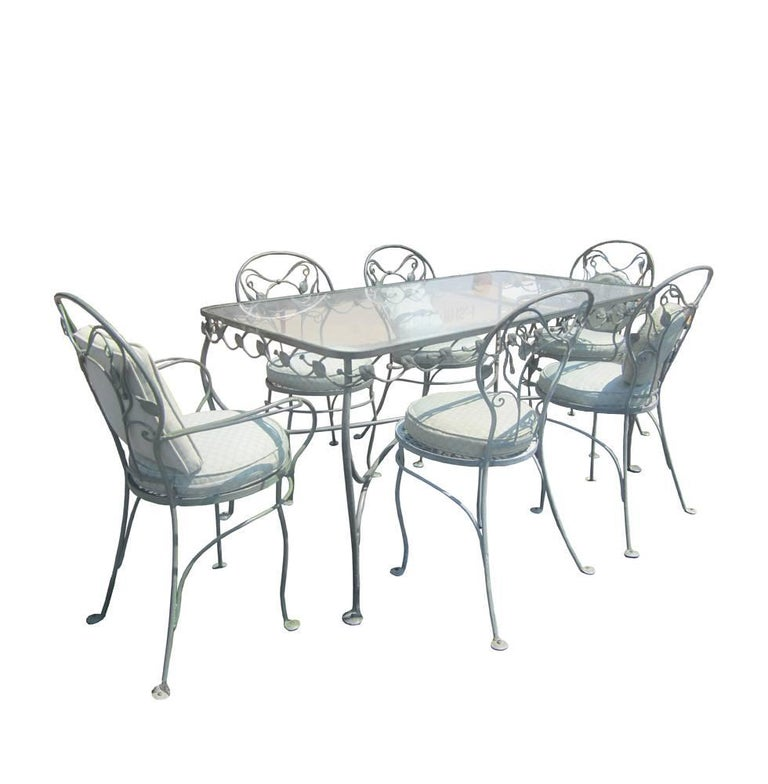 A set of eight vintage Salterini wrought iron patio chairs with a leaf motif and seat cushions. See wrought iron and glass dining table also by Salterini also available.