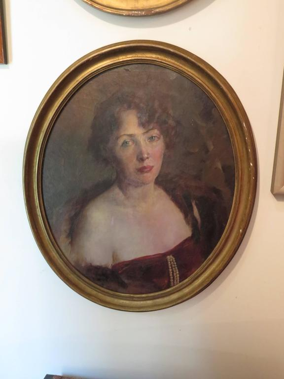 Large oval giltwood framed portrait of woman. This is an oil painting on canvas wrapped on to a board.