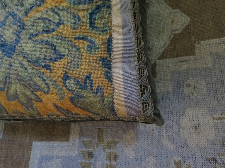 19th century large needlepoint pillow in bold cobalt and gold. Needlepoint is framed with vintage canvas ribbon and decorative metallic trim. Pillow is backed with a rich brown silk velvet. Down filled.