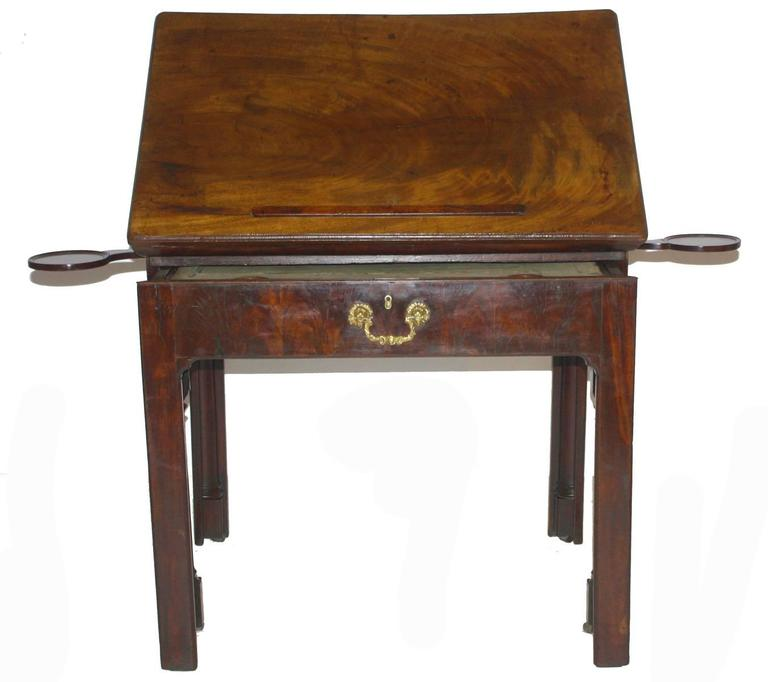 an 18th century, English architect's drawing table / desk of mahogany, the hinged top adjusts to various angles, the table / drawer extends as a writing/working surface with old worn baize top, it opens to reveal compartments for storage, small