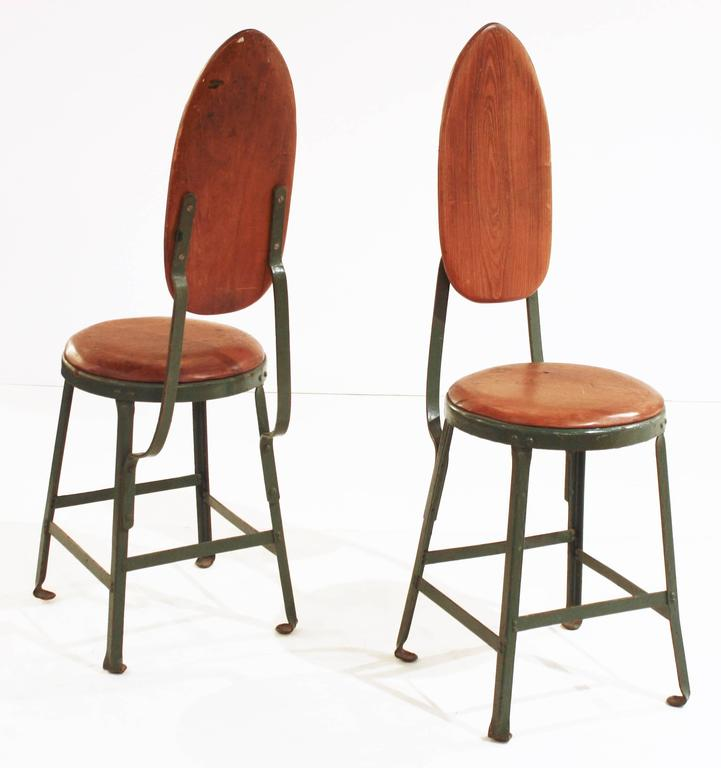 A pair of Mid-Century Modern painted steel and wood French side chairs in the style of Jean Prouve.