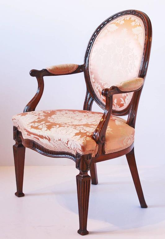 A George III mahogany open armchair in the manner of Thomas Chippendale, oval rose floral silk damask later upholstered back, the cresting with husk entwined ring, with down swept padded arm supports over a fluted seat rail with central patera