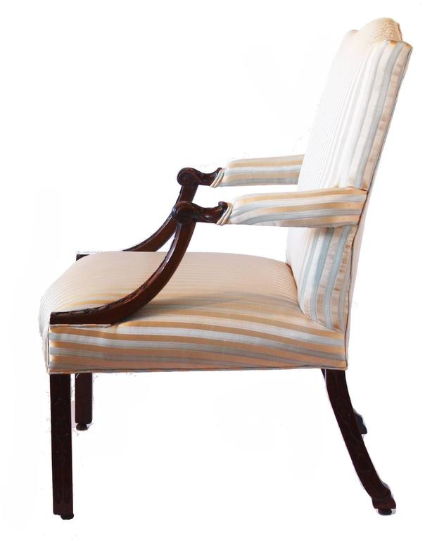 A George III mahogany library armchair in the manner of Thomas Chippendale, the rectangular padded back and seat covered in a later pale green and gold silk striped pattern fabric, the partially padded arms and coiled acanthus handholds above down