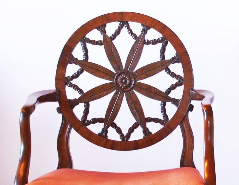 A pair of George III mahogany Hepplewhite period wheel back open elbow chair in the manner of Robert Adam (Scottish 1728-1792), bearing the characteristic circular pierced splat enclosing palm leaves radiating from a central patera and intersected