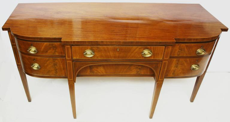 A Georgian sideboard of bookmatched crotch / flame mahogany. Wide center drawer, over an arched recessed drawer, flanked on right by a curved cellarette and a drawer and door on left, resting on tall tapered square legs. Boxwood stringing around