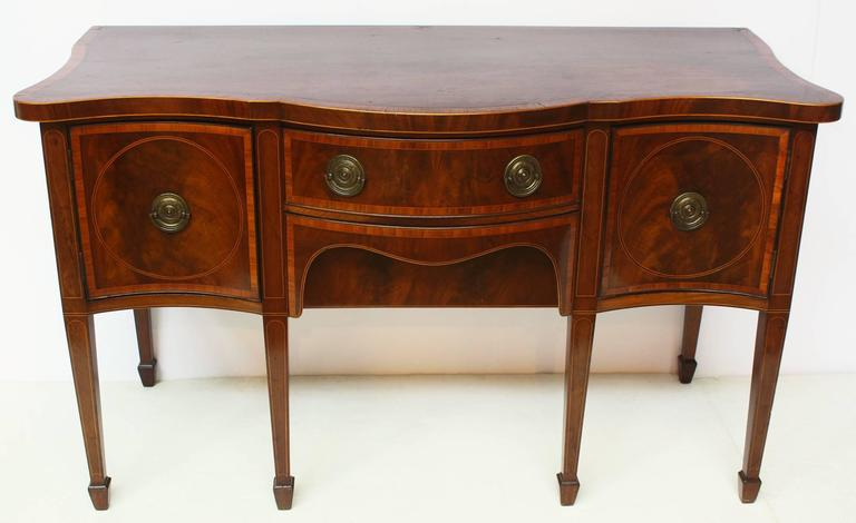 An English George III period mahogany sideboard inlaid in ebony and satinwood, with a bow fronted central drawer flanked by two serpentine fronted hinged doors each containing fitted pull-out trays. All rests on six square tapered legs and spade