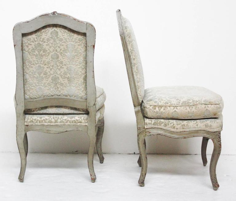 A pair of period Louis XV chairs, carved and painted frames (grey-blue) with loose cushion seats of cut velvet damask in pale grey-blue appears almost silver.