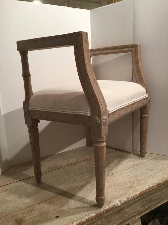 Period late 18th century Gustavian stool in original paint patina. The arms and legs have beautiful carved detail. Recently, upholstered in antique French white linen.