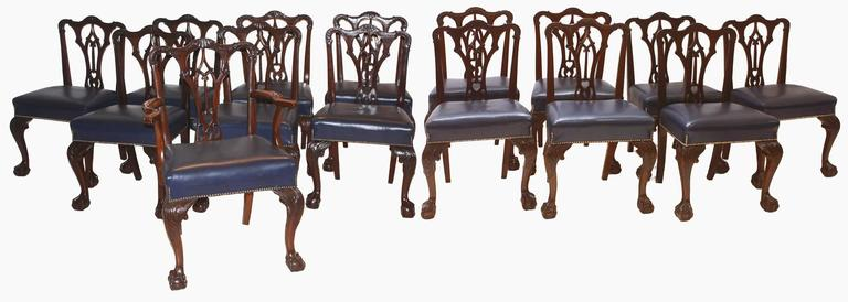 Set of fourteen (14) Irish George II style side chairs with blue leather seats upholstered over the rail with nailhead trim, heavily carved, pierced back splats, carved cabriole legs with ball and claw feet