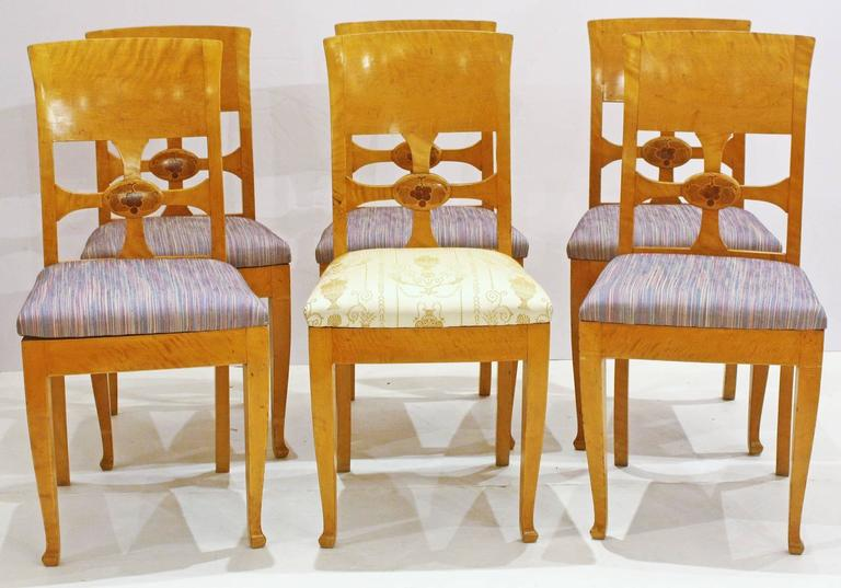 Chairs by cabinetmaker Anton Kjaer, Copenhagen, Denmark, a set of six birch chairs with panel backs, open cross with inlaid grapes and leaves in circle, metal tag from maker.