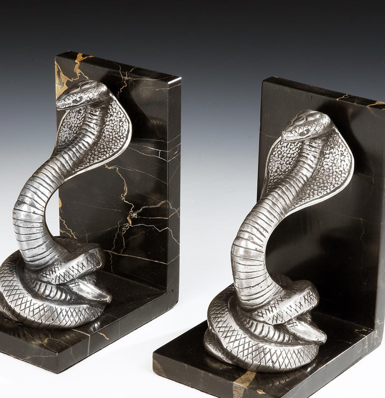Irénée Rochard (French, 1906-1984)  A pair of incredibly stylish Art Deco bookends in the form of King Cobras, the detailed snakes in patinated bronze, are shown in a striking position, and set on portoro nero marble bases, French, circa 1930.