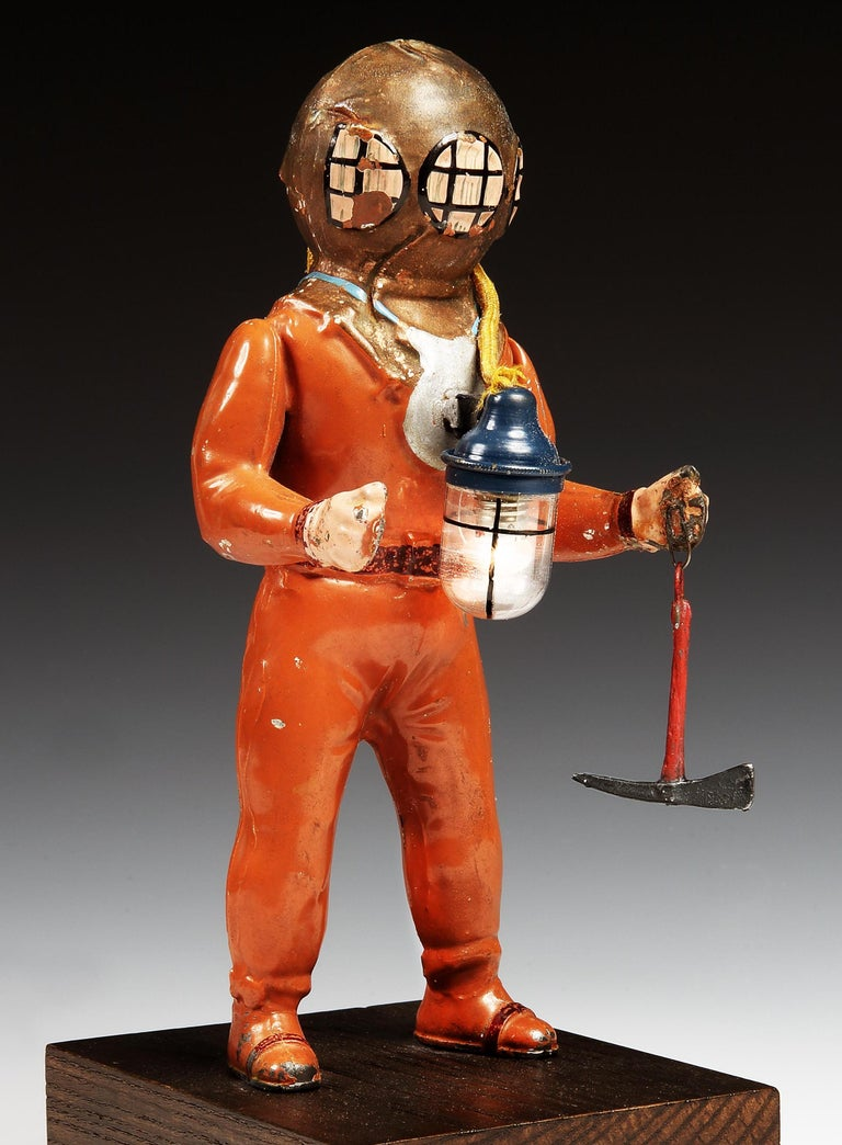 Fleischmann of Nuremberg.  An extremely desirable tinplate toy deep sea diver, dressed in 1940s period suit and helmet with all-original paint finish, the figure with diver's pick axe in one hand, simulated dive-weights around his neck, fixed to a