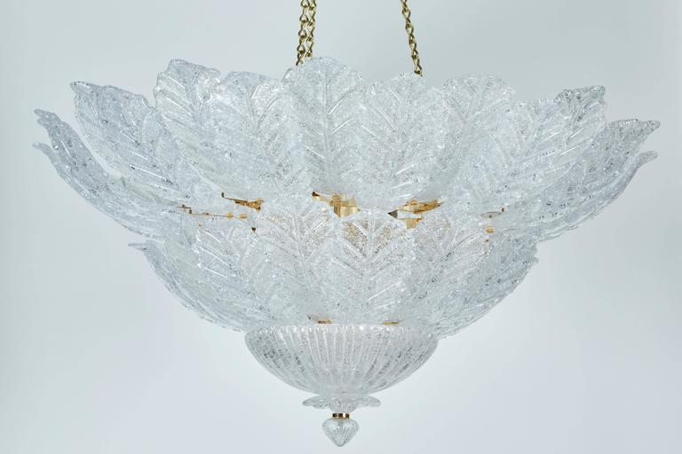 This Italian elegant chandelier with foliage design glass shapes held up by a brass fixture.
