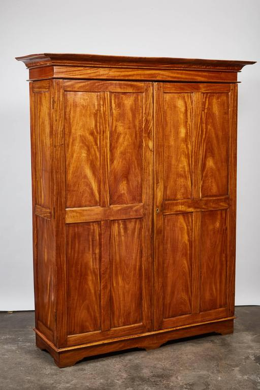 This simple yet elegant two-door satinwood cabinet from 19th century British Colonial Sri Lanka has a pair of eight carved wood panel doors and sits on a set of six rectangular legs.