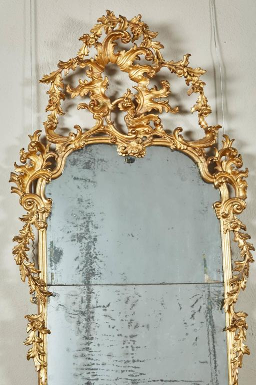 This giltwood Rococo mirror from mid-18th century Italy is a rectangular mirror surmounted by a large pierced rocaille with foliage garland extending downward toward simply decorated sides; the mirror plate in two sections; the lower frame section