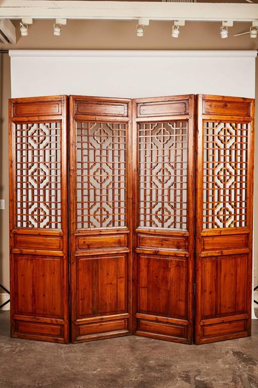 A set of 12 brown double-sided late 19th century carved Chinese screens that feature an upper portion of intricate geometrical patterns and a lower portion consisting of solid wood panels.