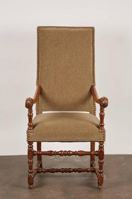An 18th century French carved walnut armchair with handsomely turned front legs and stretchers. Each arm features a stylized acanthus hand rest. The chair features new upholstery with nailhead trim.